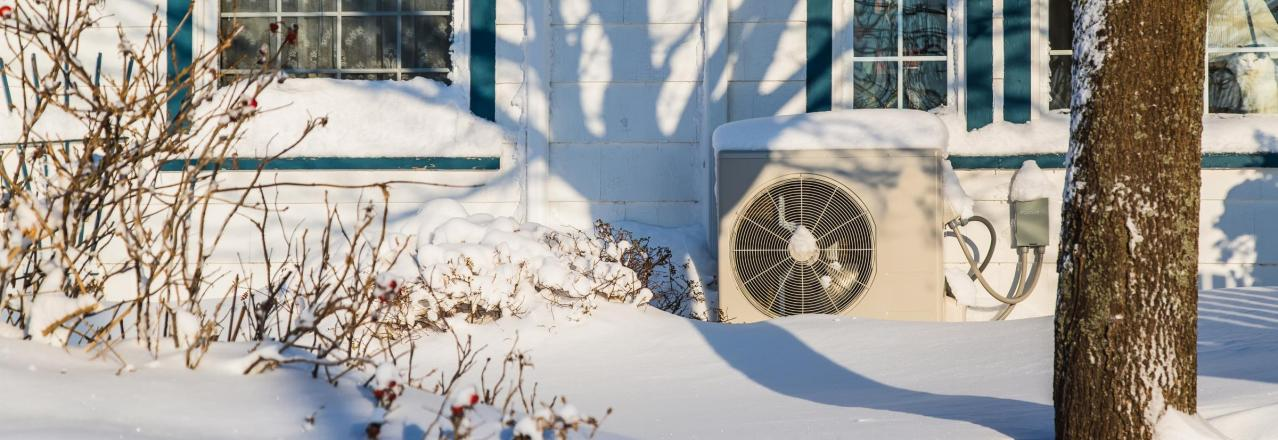 outdoor heat pump unit covered in snow outside of a home