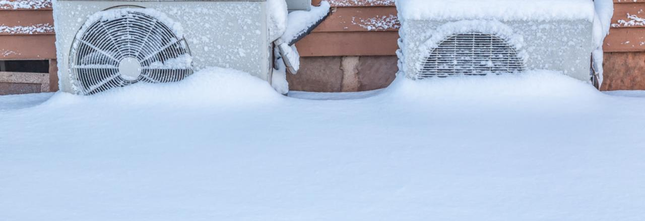 Two exterior residential heat pumps buried in snow